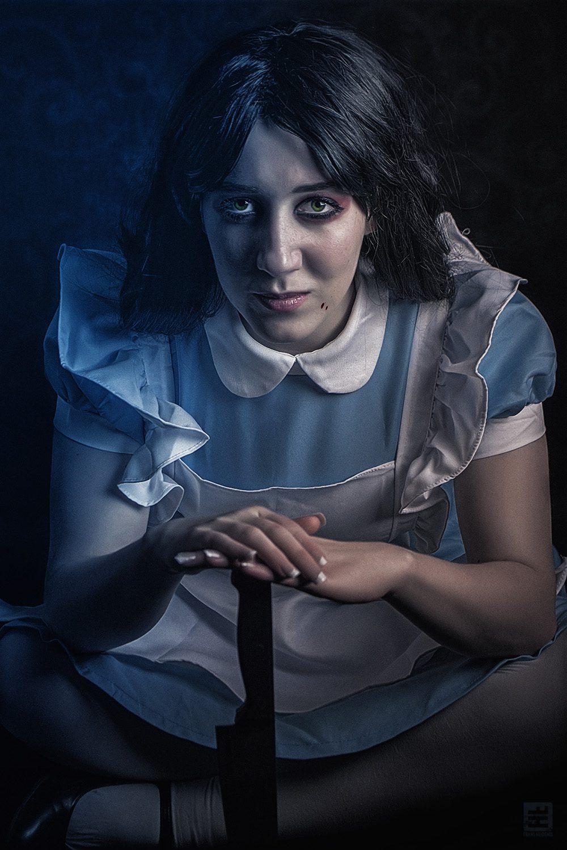 Alice the Madness cosplay. Alice zit met voor zich een groot mes met bloedspetters