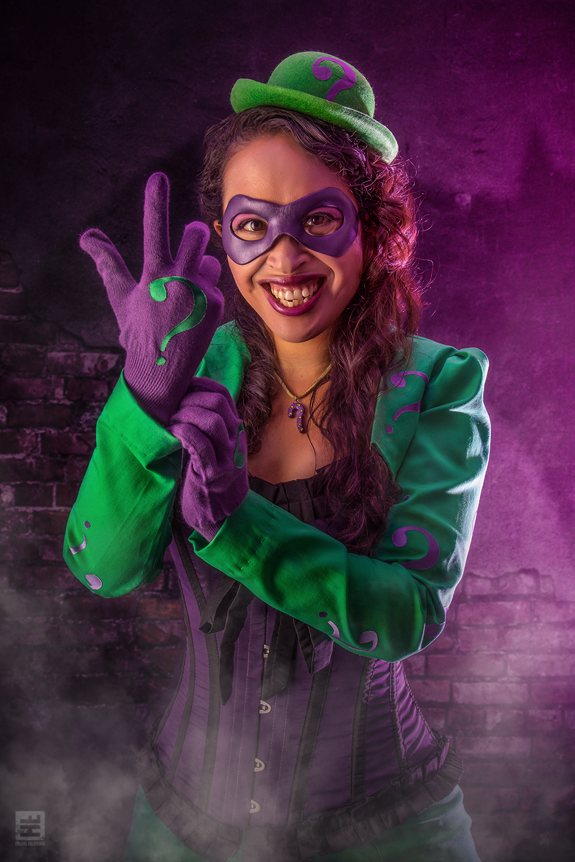Vrouwelijke versie van The Riddler. Verteld een raadsel met de vingers in de lucht.