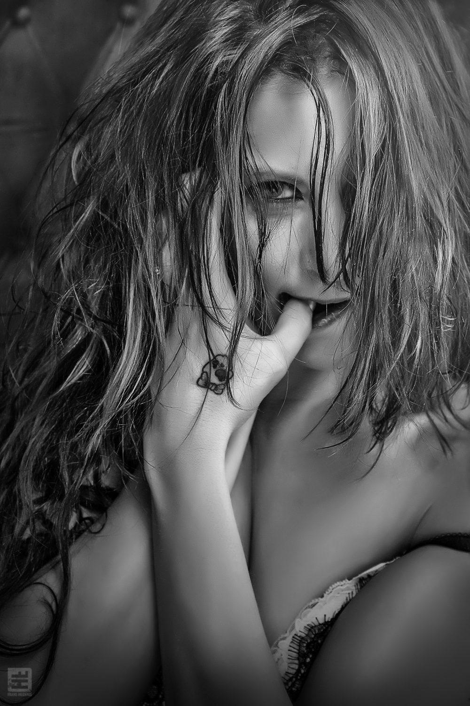 Glamour fotografie. Portret shot van een sensuele pose van een vrouw met een tattoo op haar hand.