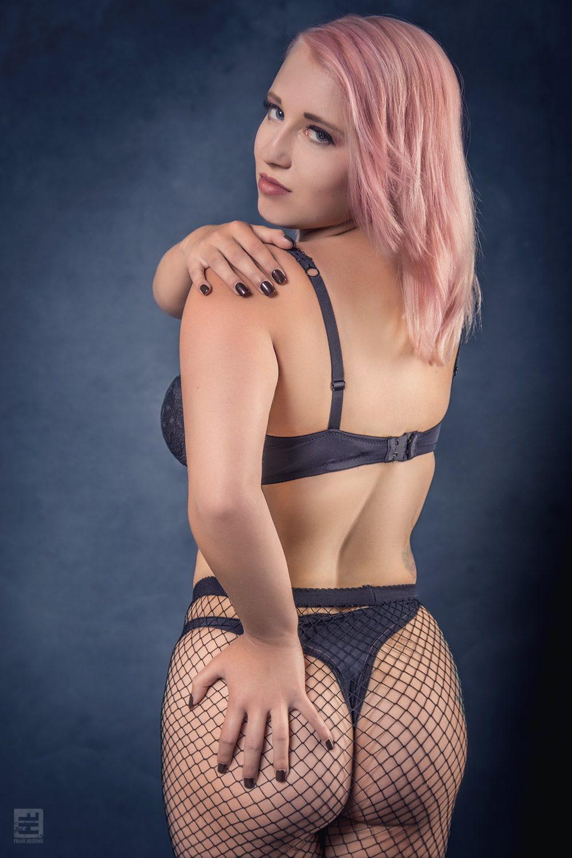 Glamour fotografie. Jong model met roze haar in sexy lingerie met netkousen in verleidelijke pose