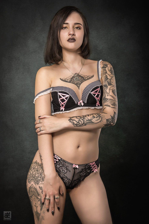 Glamour fotografie. Getinte vrouw met tattoos in zwart met roze sexy setje in uitdagende dominante pose.