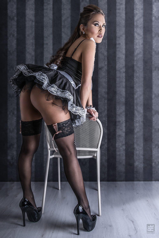 Glamour fotografie. Jennifer Namen in sexy Frans kamermeisje outfit in verleidelijke pose tegen een stoel.