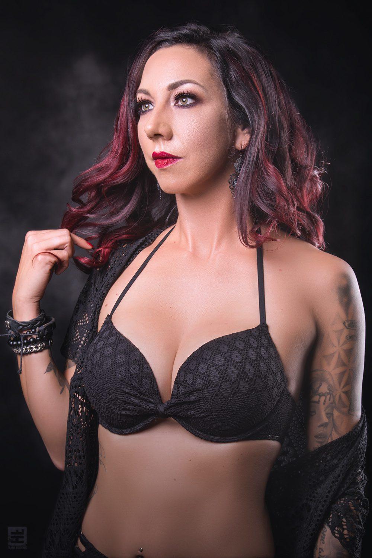 Glamour fotografie. sexy vrouw In sexy kanten lingerie, kanten kamerjasje spelend met haar rood geverfde haar