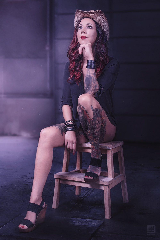 Glamour fotografie. Getatoeëerde vrouw met cowboy hoed in zwart sexy lingerie setje zittend op een kruk. En gephotoshopt in een moderne boerderij schuur.