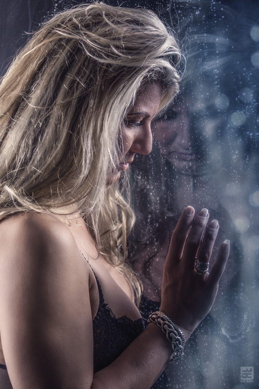 Glamour fotografie. Vrouw kijkend naar buiten in lingerie door het raam met regendruppels.
