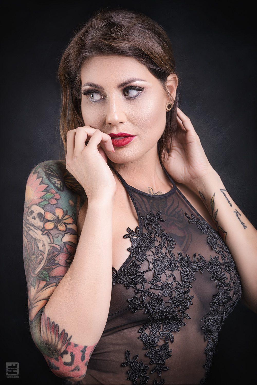 Glamour fotografie. Portret van een getatoeëerde mooie vrouw in doorschijnende lingerie in sexy pose