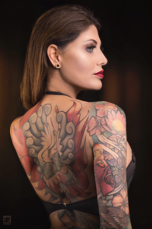 Glamour fotografie. Portret van een getatoeëerde mooie vrouw in doorschijnende lingerie in sexy pose met een grote feniks op haar rug.