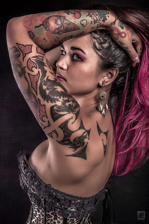 Glamour fotografie. Licht Aziatische getatoeëerde vrouw in tijgerprint korset met fel roze haar in verleidelijke zijaanzicht pose.