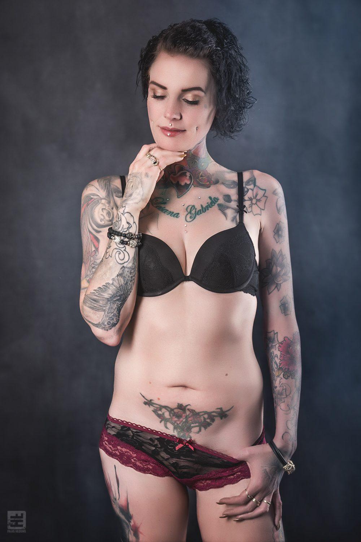 Glamour fotografie. Getatoeëerde moeder met zwart kanten bh en rode slip in sexy pose.