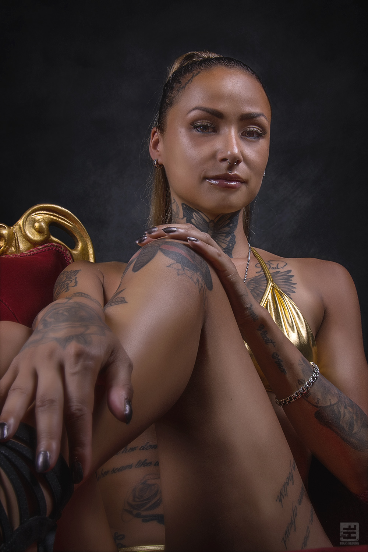 Glamour fotografie. Donker getinte getatoeëerde vrouw in gouden bikini zitten op een rode fluwelen koningsstoel