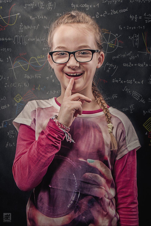 Kind portret fotografie. Meisje met een wiskunde knobbel tegen een wiskunde achtergrond gezet als genie.