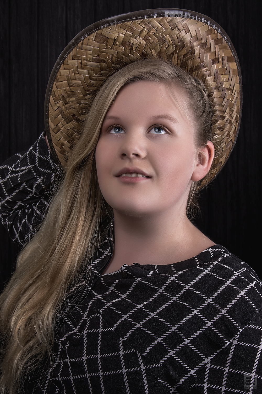 Kind portret fotografie. Meisje met rieten cowboy hoed en lang haar.