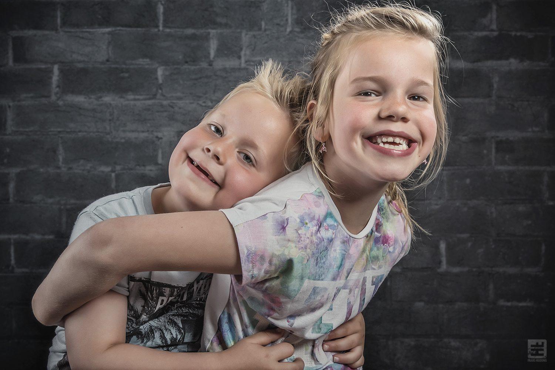 Kind portret fotografie. Grote zus met klein broertje lekker gek doen in de studio. Gewoon kind zijn.