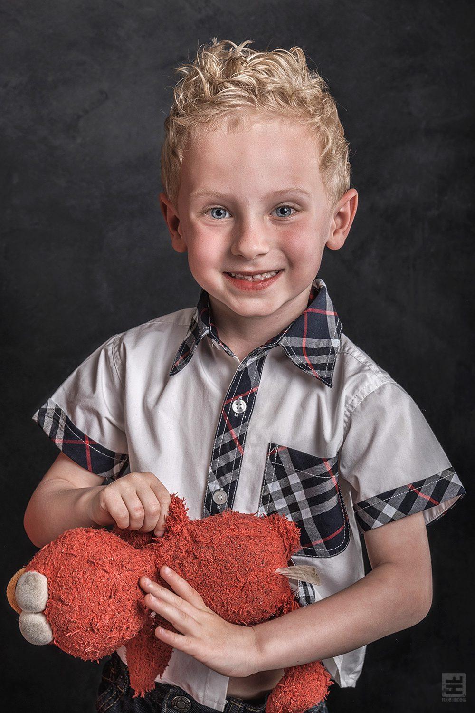 Kind portret fotografie. Jonge krullenbol met als knuffel elmo van de muppetshow of is het nou sesamstraat.