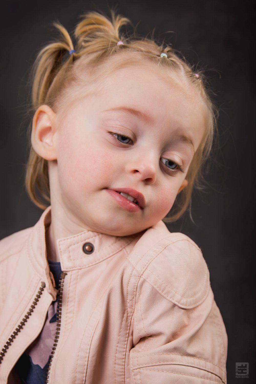 Kind portret fotografie. Lief klein schattig meisje is een beetje verlegen voor de camera.