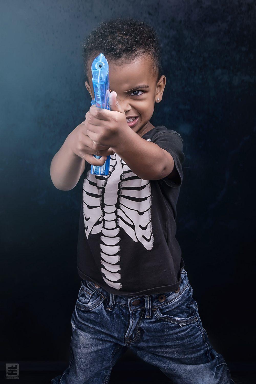 Kind portret fotografie. O dat begint al jong, handen omhoog of ik schiet. Gelukkig is het maar een waterpistool, wel effe schrikken.