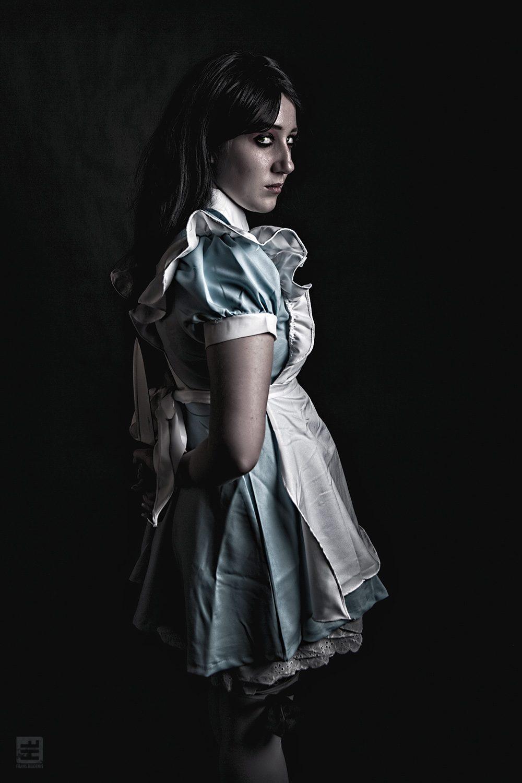 Alice the Madness cosplay. Alice staat in het donker met een mes achter haar rug.