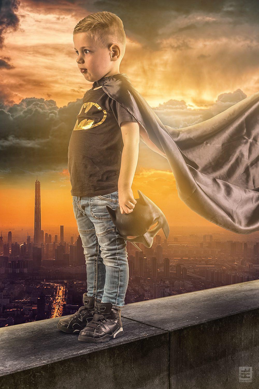 Batman Tijs - Jongetje van 6 jaar in Batman shirt, cape en masker staand op een richel kijkend over Gotham