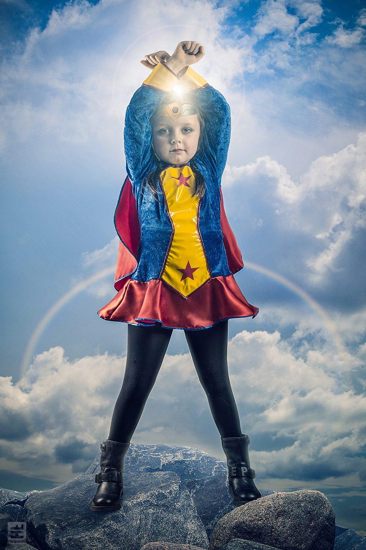 Wonderwoman Daisy mesje van 5 jaar in een vintage outfit van wonderwoman. staand op een berg hoog in de lucht.