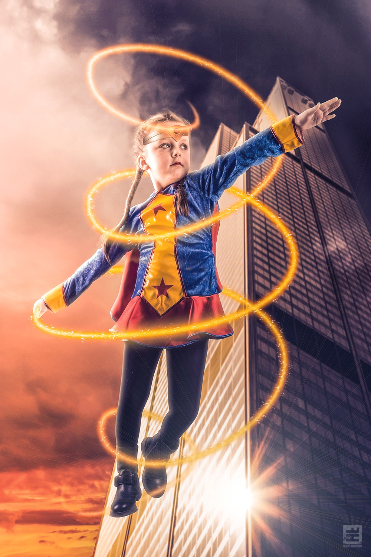 Wonderwoman Daisy. Meisje van 5 jaar vliegend tussen de hoge flats met in haar hand de gouden lasso compleet in vintage wonderwoman outfit