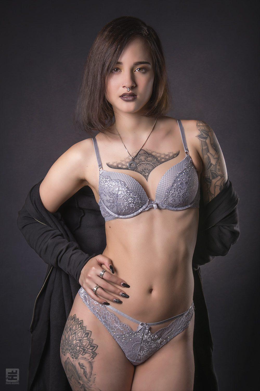 Glamour fotografie. Getinte vrouw met tattoos in blauwe grijze lingerie in uitdagende dominante pose.