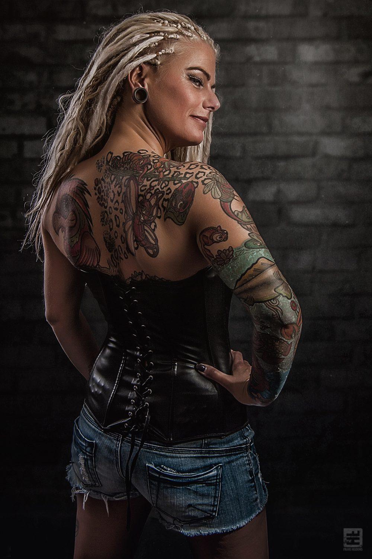 Glamour fotografie. Stoere getatoeëerde vrouw met dreadlocks in lederen korset en hotpants.