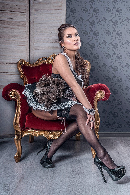 Glamour fotografie. Jennifer Namen in sexy Frans kamermeisje outfit in uitdagende pose op een rode koningsstoel met bijpassende plumeau