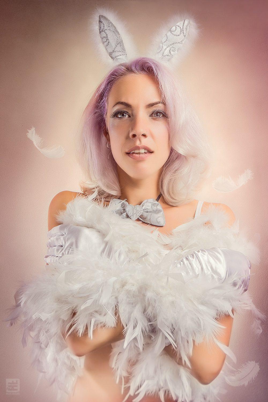 Glamour fotografie.Portret van een model met licht roze haar, bunny oortjes op haar hoofd en een veren boa om haar heen