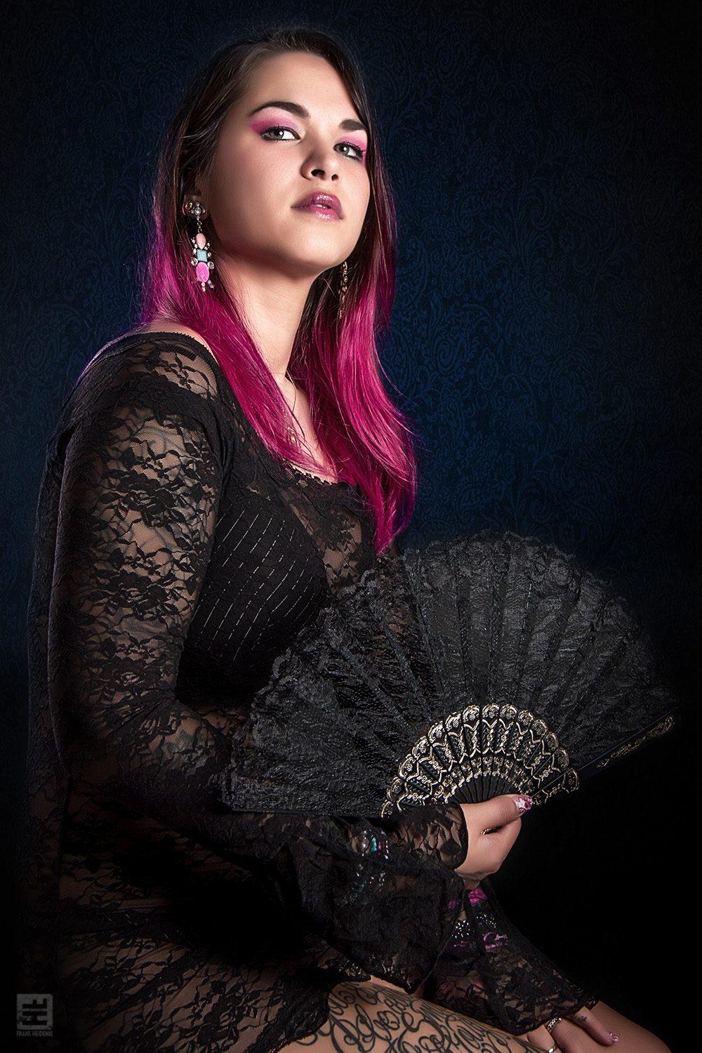 Glamour fotografie. Licht Aziatische vrouw in zwart jurkje met fel roze haar en zwarte kanten Spaanse waaier in haar hand.