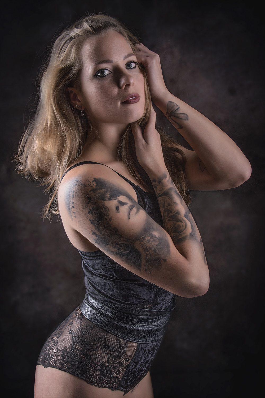 Glamour fotografie. Getatoeëerde vrouw met zwart kanten lingerie in sexy pose.