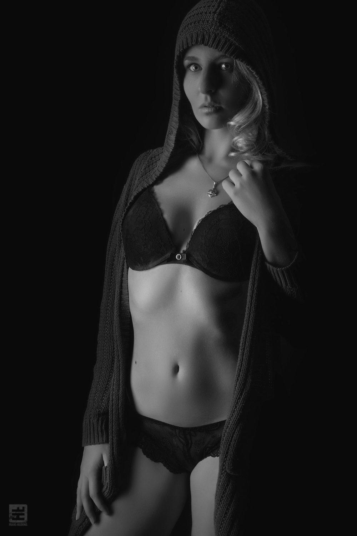 Glamour fotografie. Jong sexy model in kanten sexy lingerie en hoodie in low key gefotografeerd. Uitgevoerd in zwart/wit