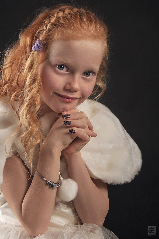 Kind portret fotografie. Roodharige meisje met de handen gevouwen kijkend in de camera.
