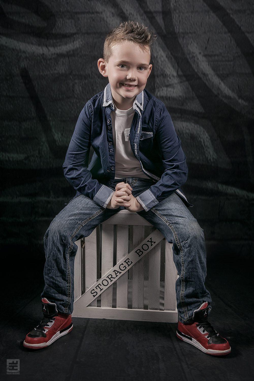 Kind portret fotografie. Stoere jongen zittend op een houten verhuiskrat. Lekker badass