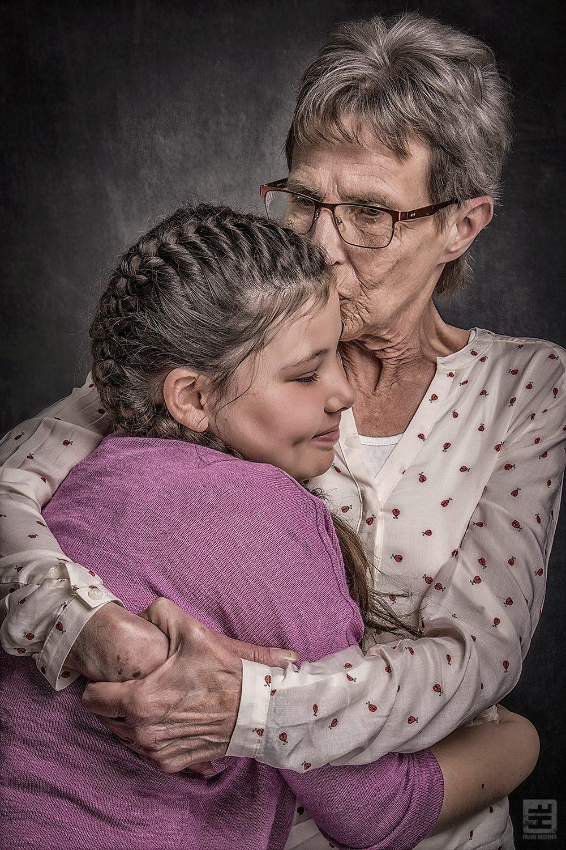 Portret Fotografie - Oma en kleindochter in een emotionele omhelzing volledig in de stijl van Frans Heidenis