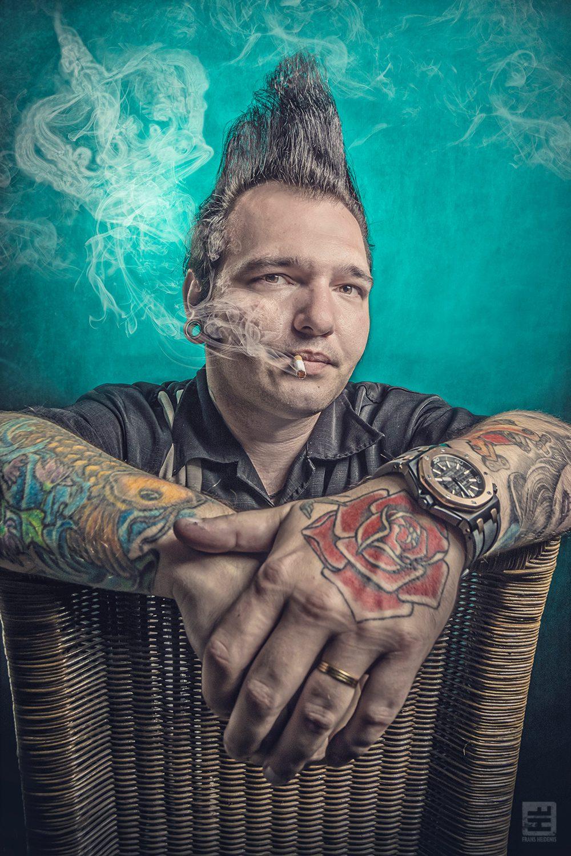 Portret Fotografie - Tattoo artiest Gerrit van Veen met grote rock 'n Roll kuif zittend op een stoel met sigaret en in de rook ervan een kroon verwerkt