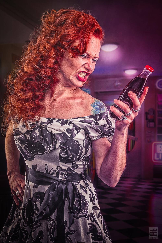 Portret Fotografie - Roodharige pin-up schreeuwend naar een flesje Coca Cola met op de achtergrond een diner