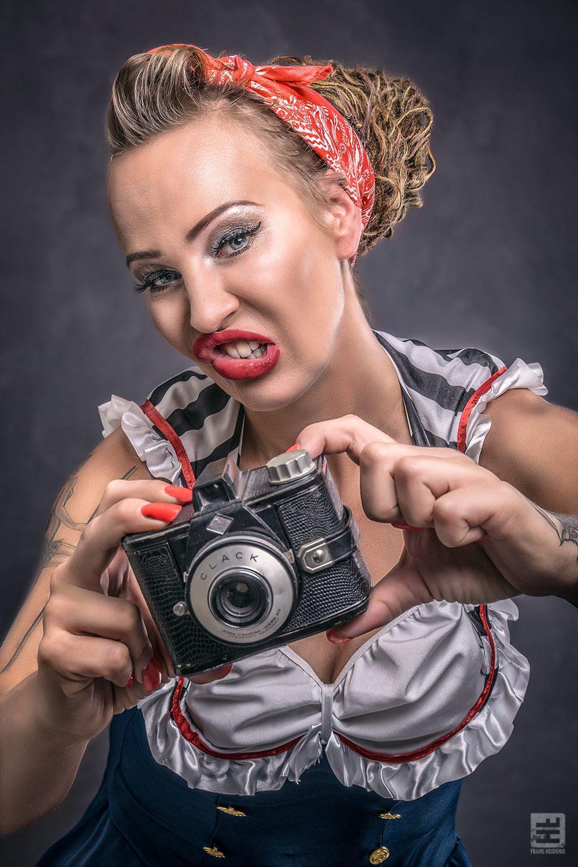 Portret Fotografie - Portret van klassieke pin-up met een ouderwetse camera in grappige pose