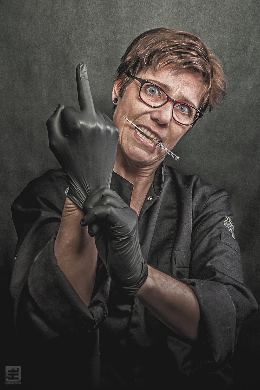 Portret Fotografie - Portret van een vrouwelijke piercer met middelvinger terwijl ze haar latex handschoen aantrekt. Tattoo Herco