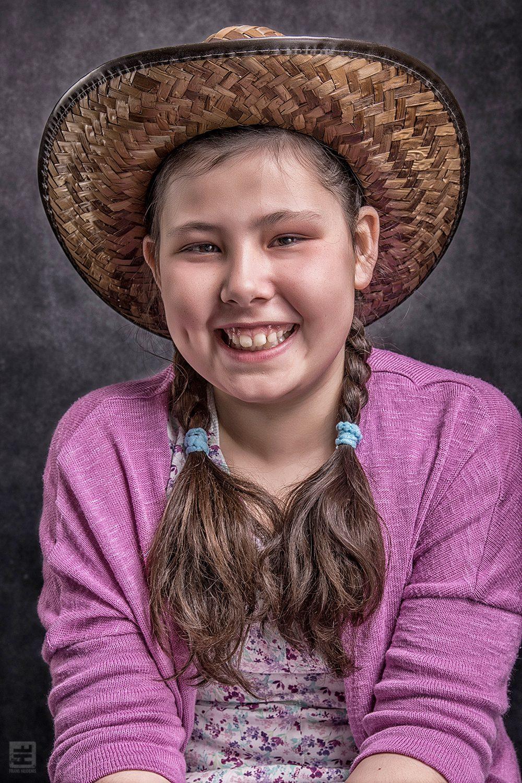 Kind portret fotografie. Meisje met 2 paardenstaartjes lachend op een stoel met een rieten cowboy hoedje op.