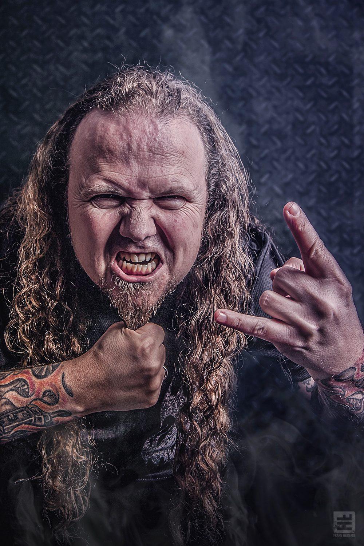 Portret Fotografie - Een echte metalhead in een stoere pose trekkend aan zijn baard met hand in teken van de hoorns