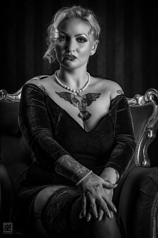 Portret Fotografie - Portret van een glamour vrouw in avondjurk en jarretels zittend op een luxe stoel in een victoriaanse kamer