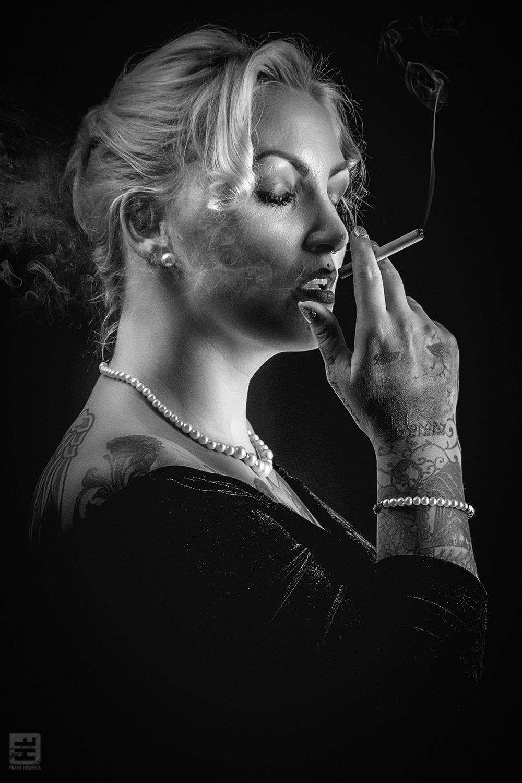 Portret Fotografie - Portret van een rokende vrouw met tattoos uitgevoerd in noir style.