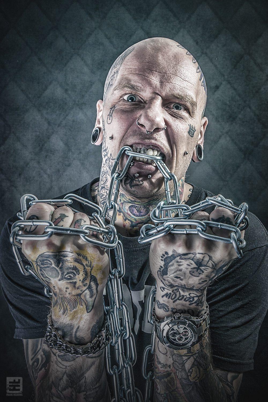 Portret Fotografie - Portret van een tattoo artiest uit belgie werkt onder de naam Royal Bastard. In zijn handen zware kettingen en is gemaakt voor promotie doeleinden.