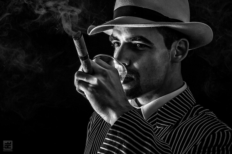 Portret Fotografie - Portret van een klassieke italiaanse maffia man in pak met whiskey en sigaar