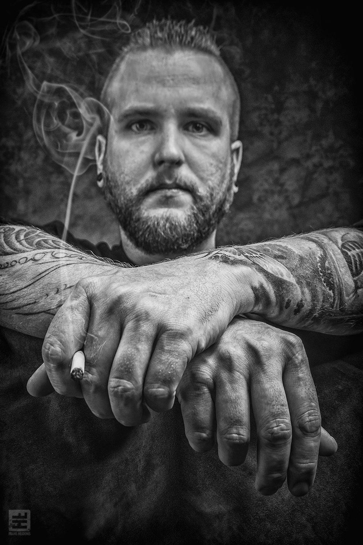 Portret Fotografie - Stoer tattoo artiest portret in zwart/wit met de nadruk op getatoeëerde handen. Limited Edition Tattoos