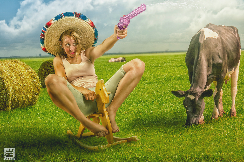 Vrouw op een kind hobbelpaard met waterpistool in een weiland gephotoshopt tussen de hooibalen en koeien.