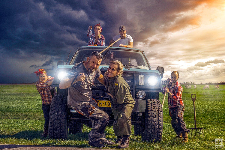 Complete familie met hond en hun geliefde pickup in een weiland. Volledig met Photoshop bewerkt tot een mooie familie foto.