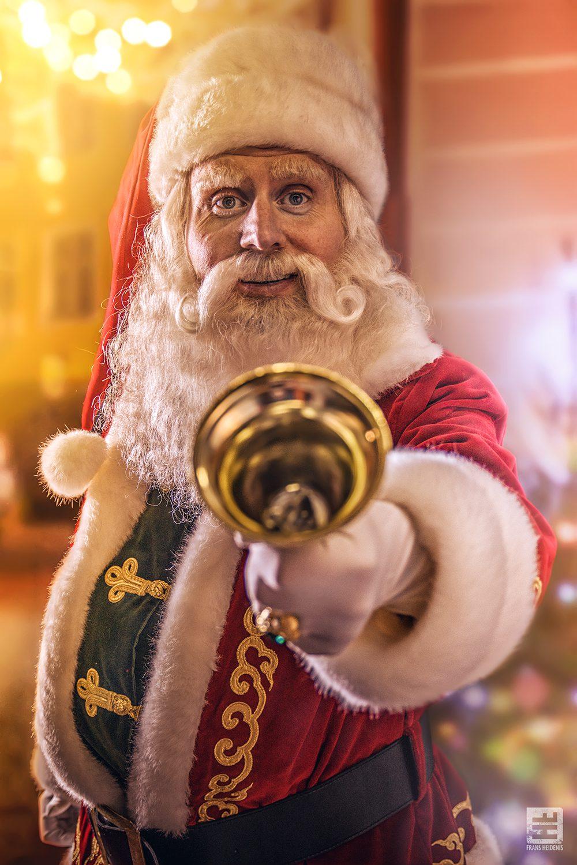 Santa claus zoals ze hem in Amerika kennen. Fel gekleurde decoratie met veel lichtjes en een bel in de hand om iedereen een vrolijk kerst te wensen.