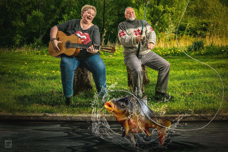 Getrouwd koppel dat langs het water muziek speelt en vist. Gefotografeerd in de studio en met Photoshop een hele scene gebouwd.