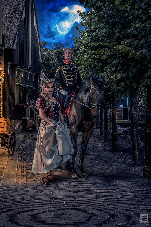 Man officier en vrouw in victoriaanse jurk. Terug in de stad. Achtergrond Zuiderzeemuseum Enkhuizen. Fotografie en Photoshop.